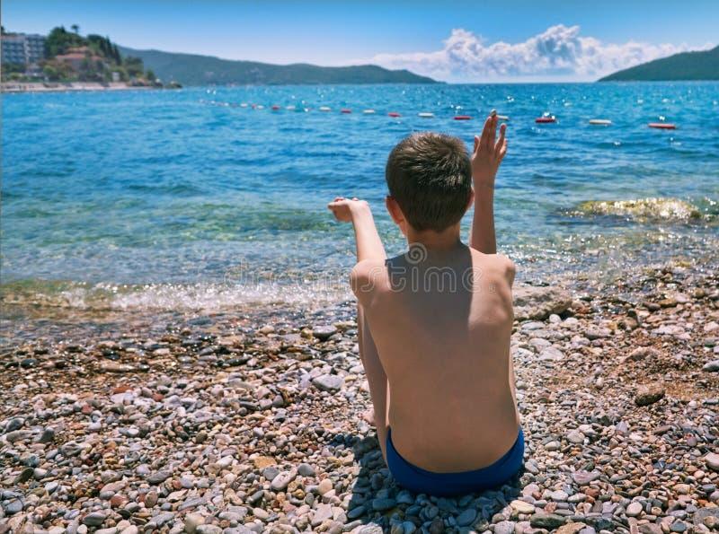 年轻在海水的男孩投掷的石头 沙漠海滩Hertseg Novi 科托尔海湾,黑山 库存图片