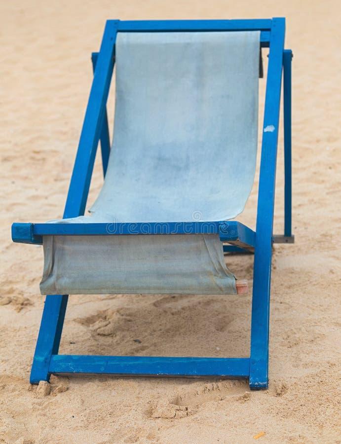 在海滩的空的蓝色deckchair 图库摄影