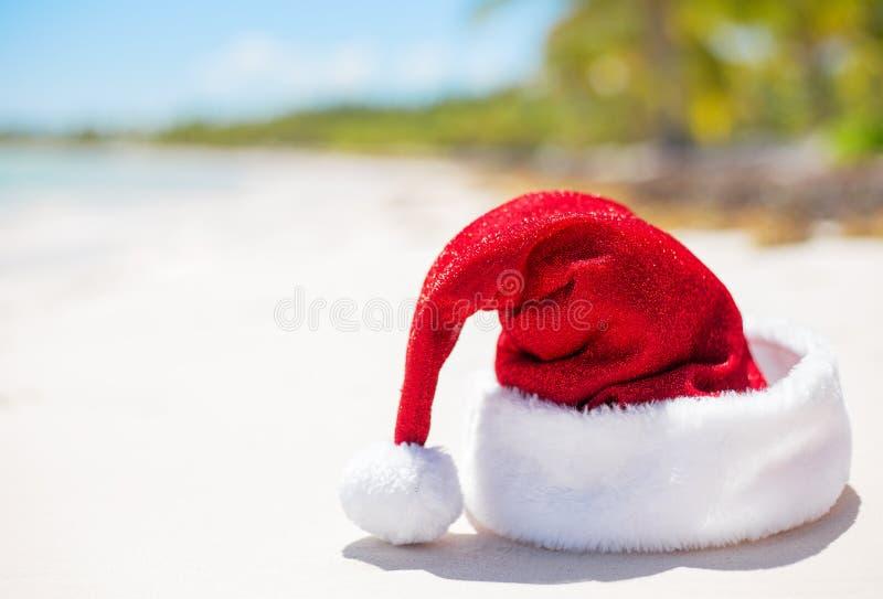 在海滩的红色圣诞老人帽子,题材为圣诞节假期和旅行 免版税图库摄影