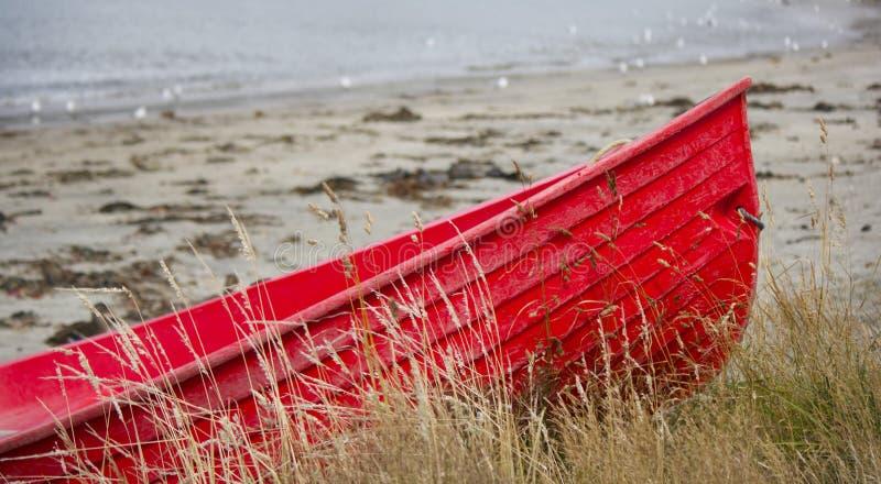 在海滩的红色小船 免版税库存照片