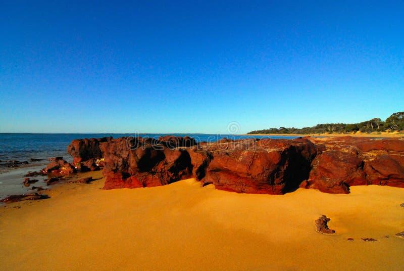 在海滩的红色岩石 免版税库存图片