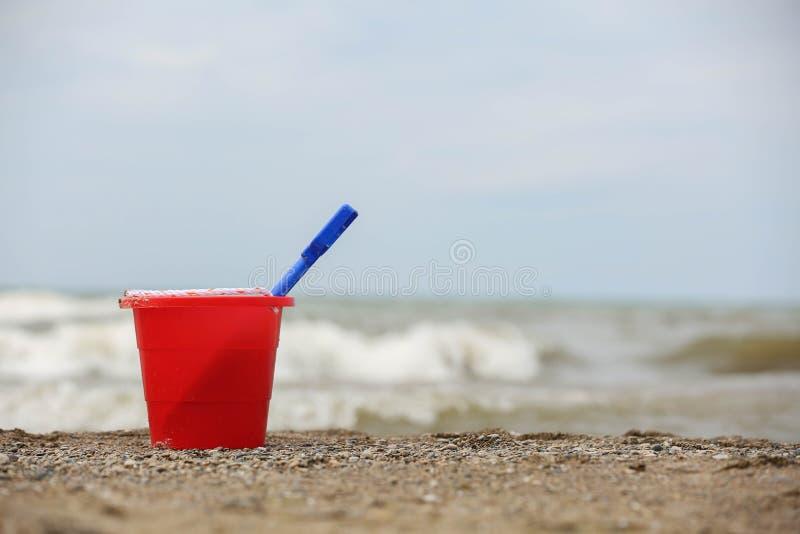 在海滩的红色桶 库存照片