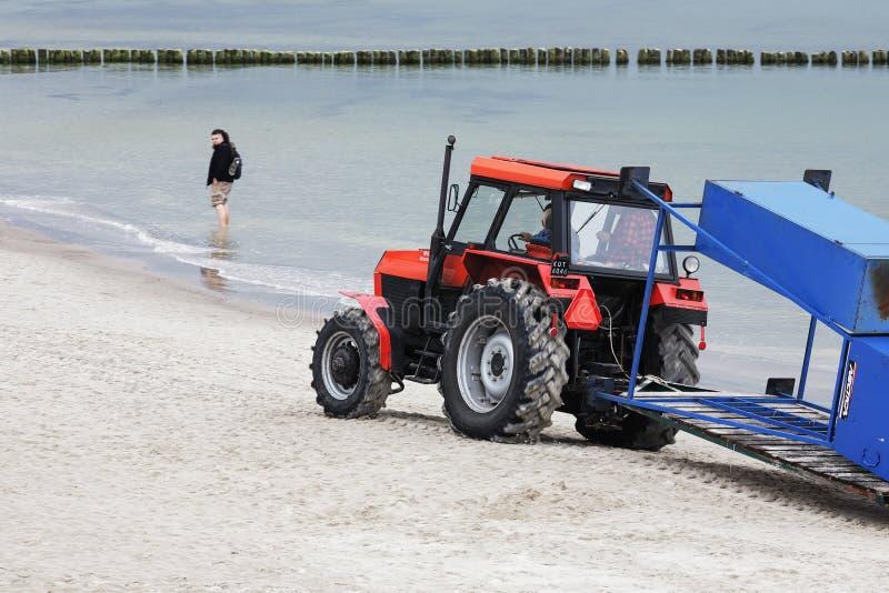 在海滩的红色绘的拖拉机由海 免版税图库摄影