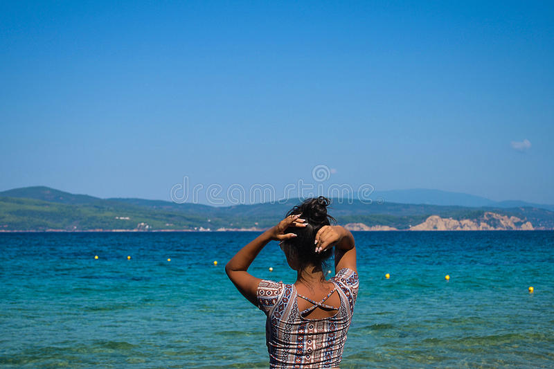 在海滩的美好的深色的模型姿势 免版税库存图片