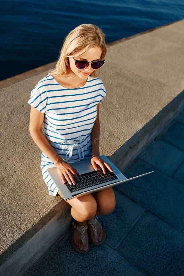 在海滩的美好的年轻女性白肤金发的开会与膝上型计算机smili 库存图片