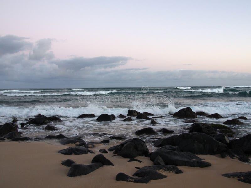 在海洋的美好的黎明有碰撞入岩石alo的波浪的 免版税库存照片