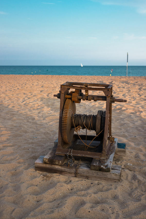 在海滩的老小船绞盘 库存图片