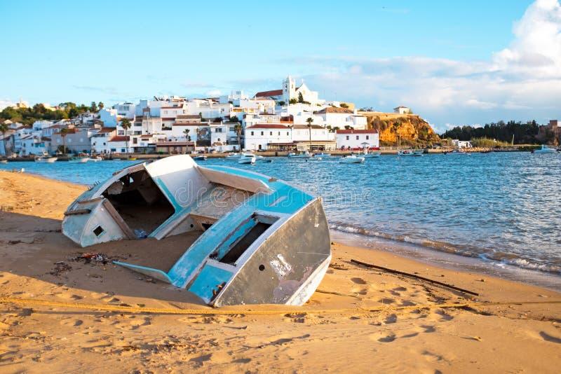 在海滩的老渔夫` s小船在Ferragudo葡萄牙附近 库存照片
