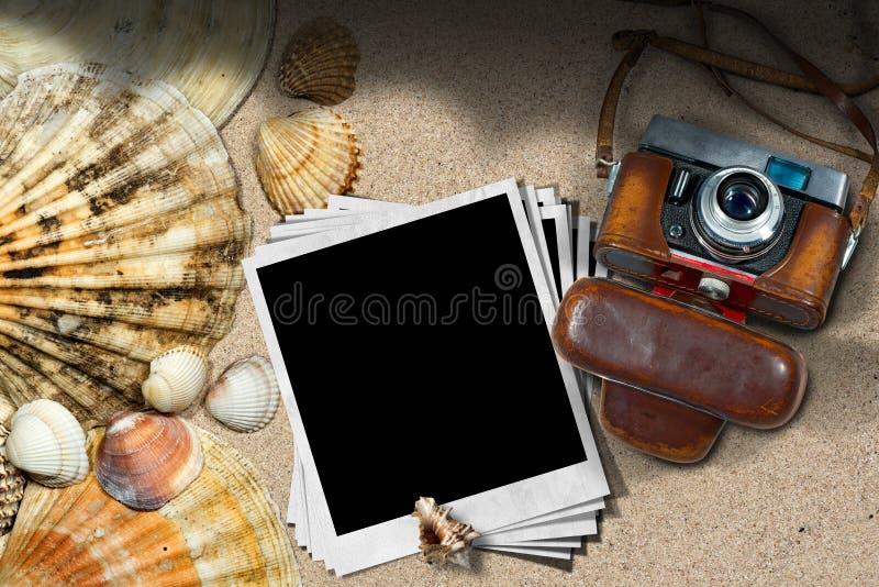 在海滩的老照相机和照片框架 免版税库存照片