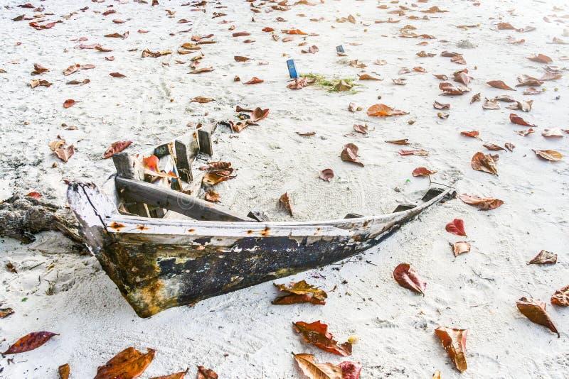 在海滩的老腐烂的小船 免版税库存图片