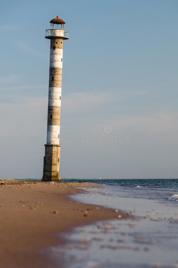 在海滩的被放弃的落的灯塔萨列马岛海岛, ES 免版税库存图片