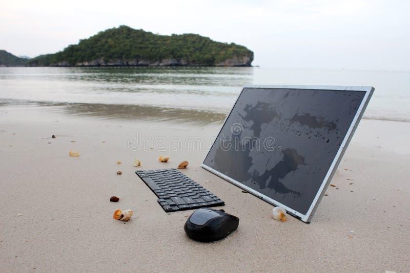在海滩的计算机 库存照片