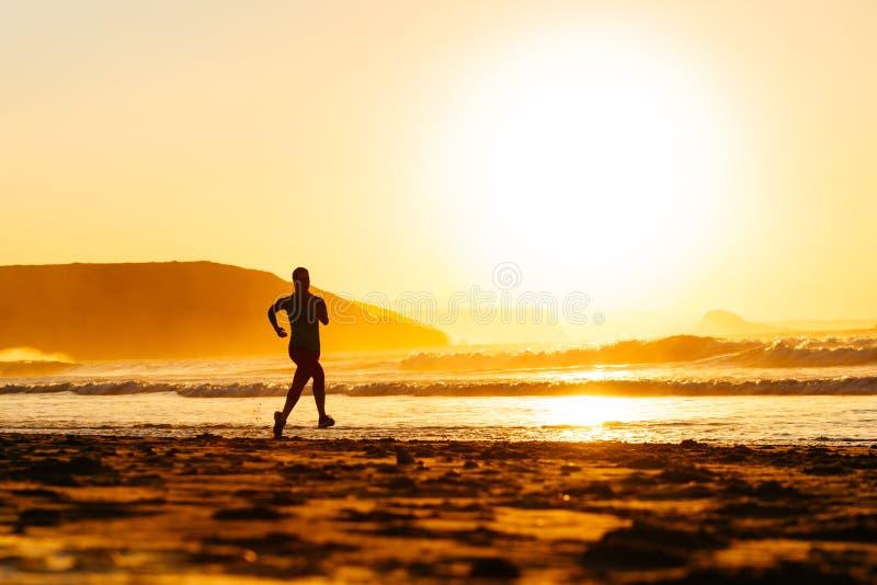 在海滩的赛跑者在日落 免版税库存照片