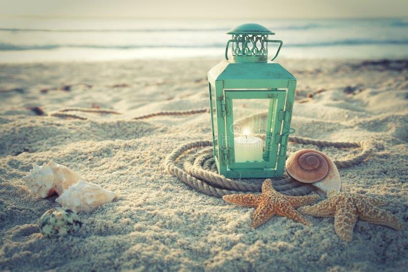 在海滩的跨被处理的在日出的灯笼与壳和绳索 免版税库存照片