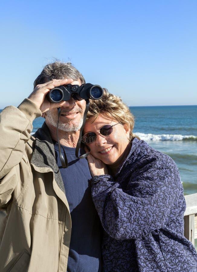 在海滩的退休的夫妇假期与双筒望远镜拥抱 库存照片