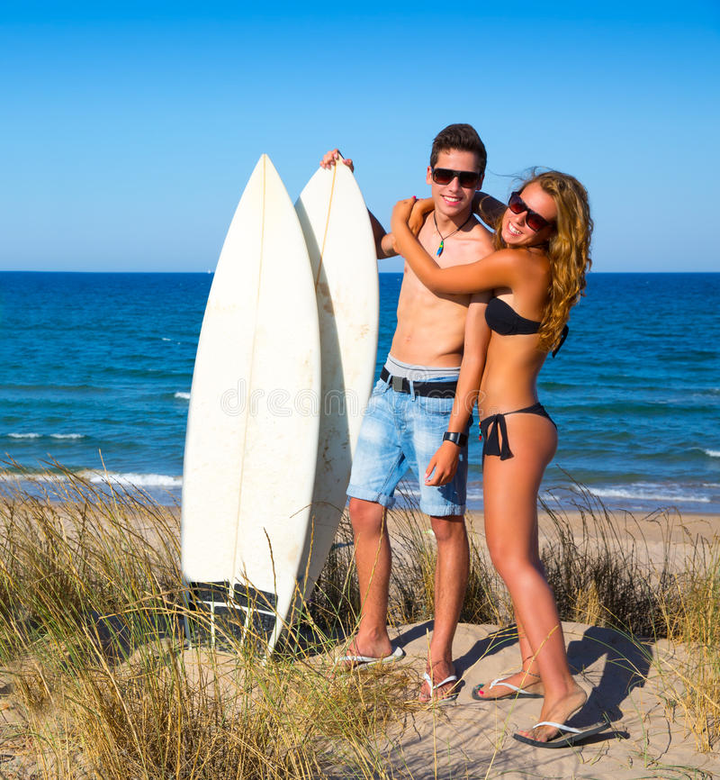 在海滩的青少年的冲浪者夫妇拥抱 免版税库存照片