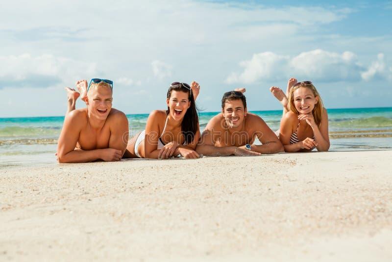在海滩的年轻愉快的朋友havin乐趣 免版税库存照片