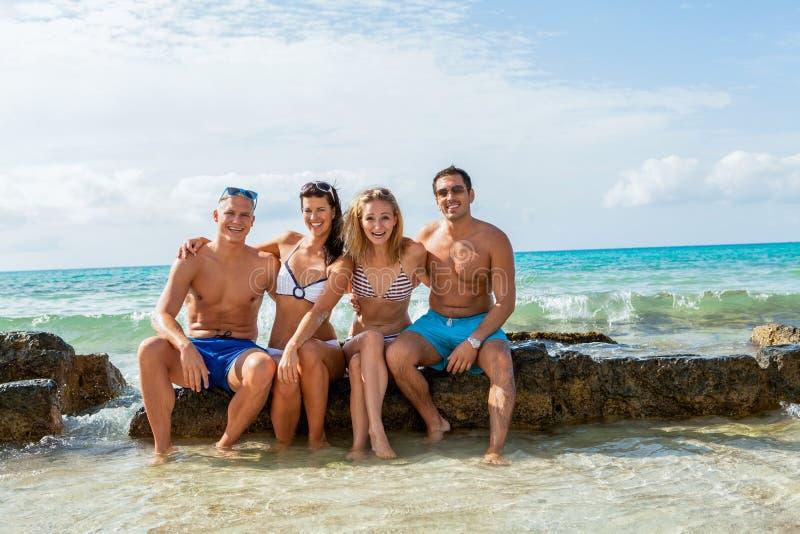 在海滩的年轻愉快的朋友havin乐趣 图库摄影