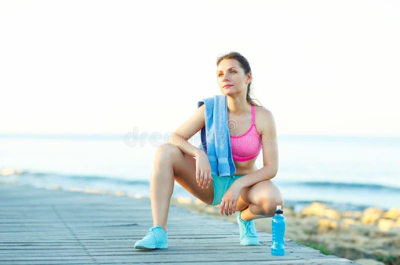 在海滩的晴朗的早晨,休息在跑以后的运动妇女 免版税库存照片