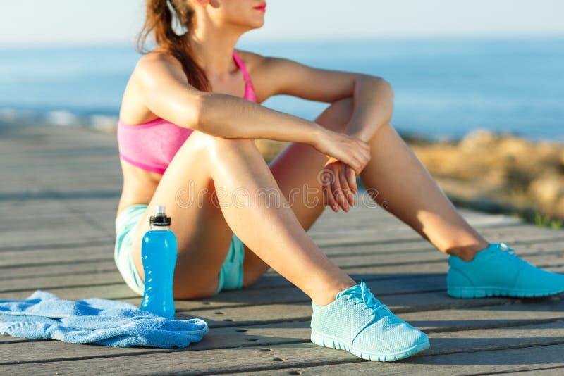 在海滩的晴朗的早晨,休息在跑以后的运动妇女 免版税库存图片