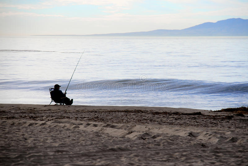 在海滩的轻松的渔夫渔 免版税图库摄影