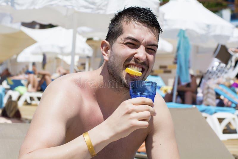 在海滩的年轻英俊的食人的新鲜的柠檬 免版税库存照片