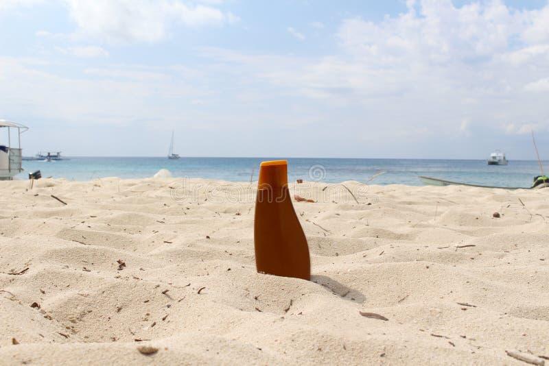 在海滩的Sunblock瓶 图库摄影