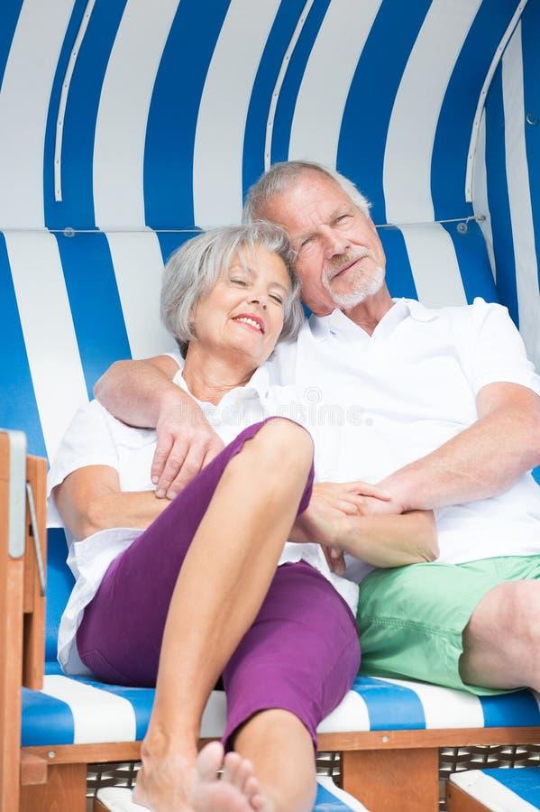 在海滩睡椅的资深夫妇 库存图片