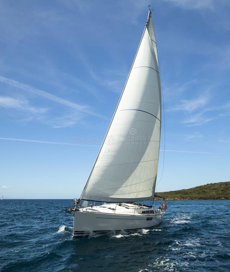 在海洋种族的豪华游艇 蓝色颜色黑暗的losed赛船会航行航行天空体育运动赢利地区 库存图片