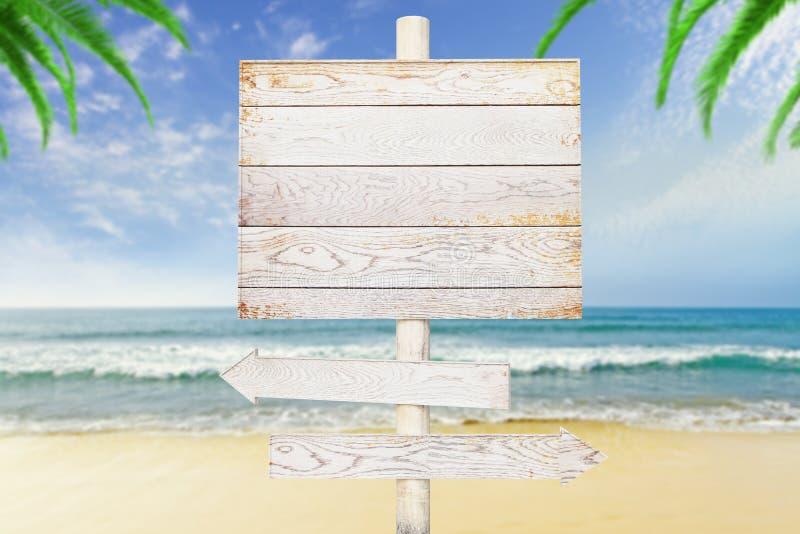 在海滩背景的木箭头标志 免版税库存照片