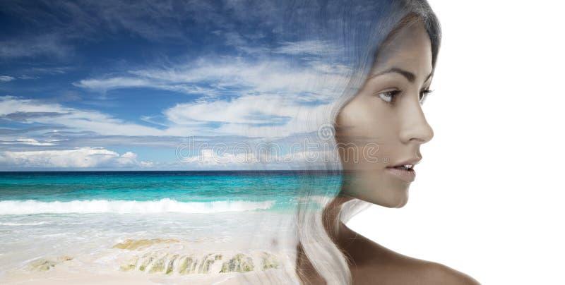 在海滩背景的美丽的少妇面孔 库存照片
