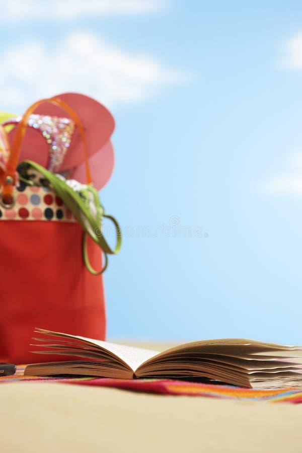 在海滩袋子旁边的开放书在海滩关闭 免版税库存照片