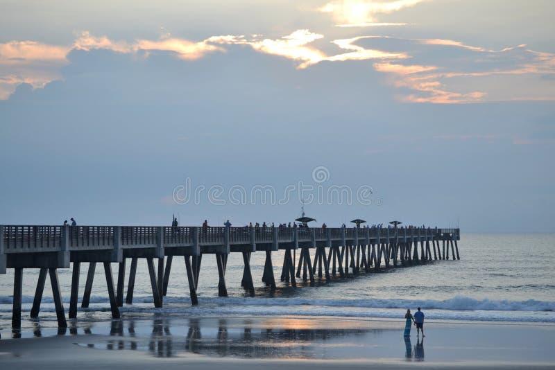 在海滩观看的日出的夫妇在码头附近 免版税库存照片