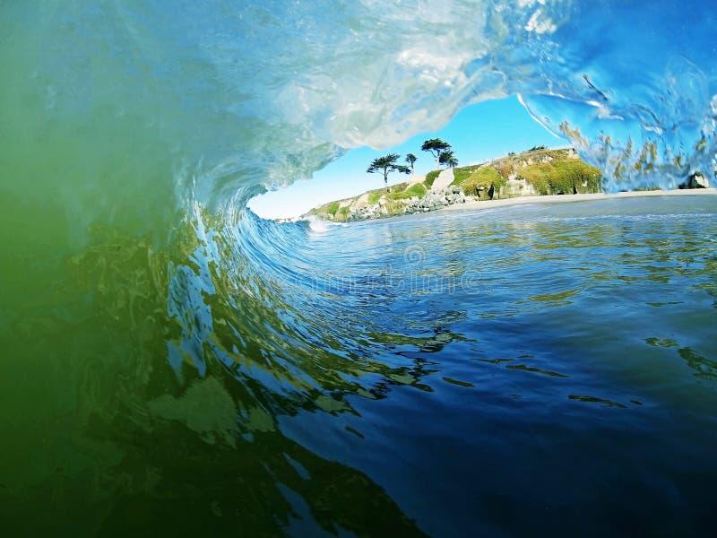在海滩附近的一个蓝色和绿色海浪断裂 免版税图库摄影