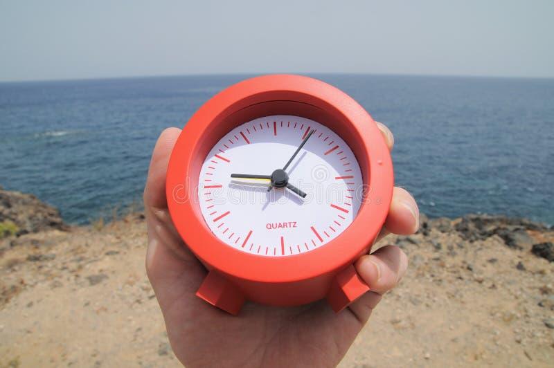 在海洋附近的红色时钟 免版税库存图片