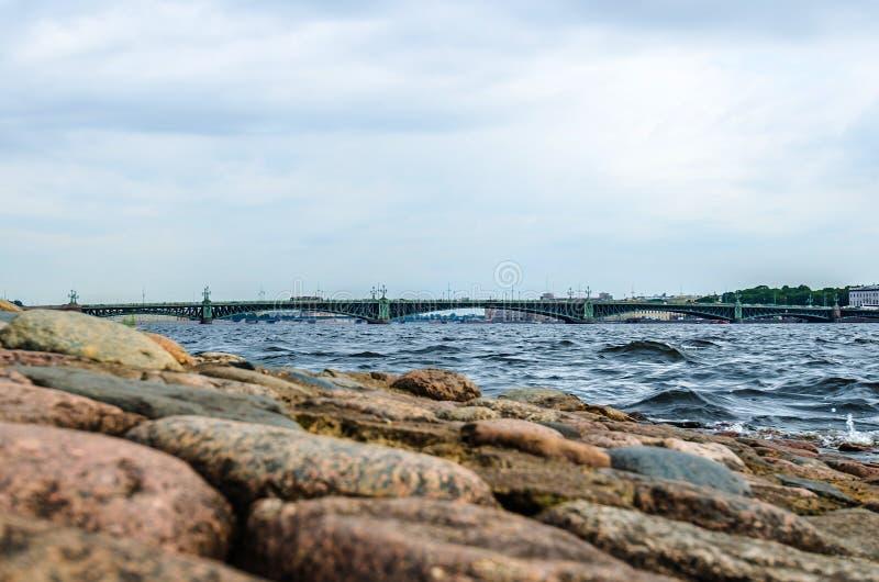 在涅瓦河的三位一体桥梁和海滩和石头 库存照片