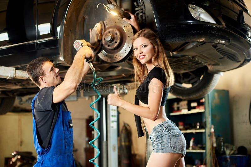 在液压悬挂的汽车修理由青年人 图库摄影