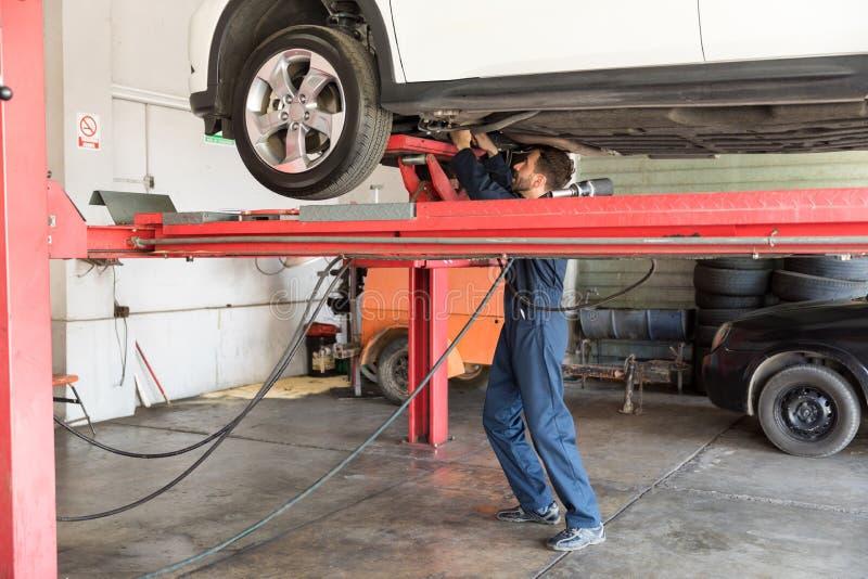 在液压悬挂的自动专家的修理的汽车在车库 免版税图库摄影