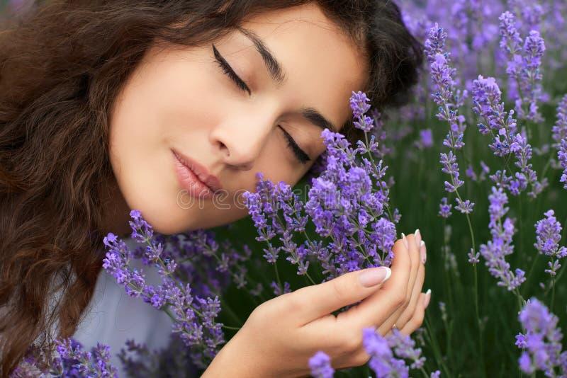 在淡紫色的美丽的少妇画象开花背景,面孔特写镜头 免版税图库摄影