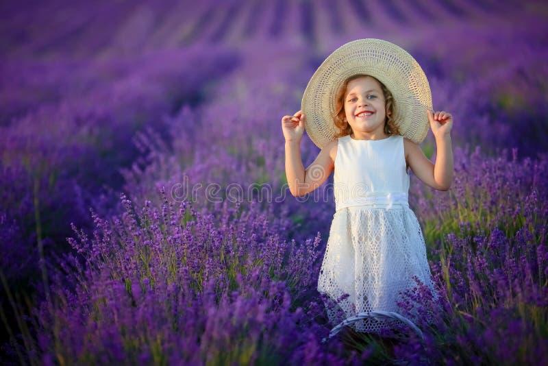 在淡紫色领域的卷曲女孩身分在白色礼服和帽子有逗人喜爱的面孔和精密头发的有淡紫色花束的和 免版税库存图片