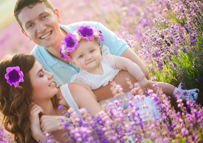 在淡紫色领域的年轻家庭 库存图片