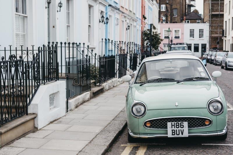 在淡色房子旁边的淡色蓝色日产费加罗在诺丁山,伦敦 库存图片