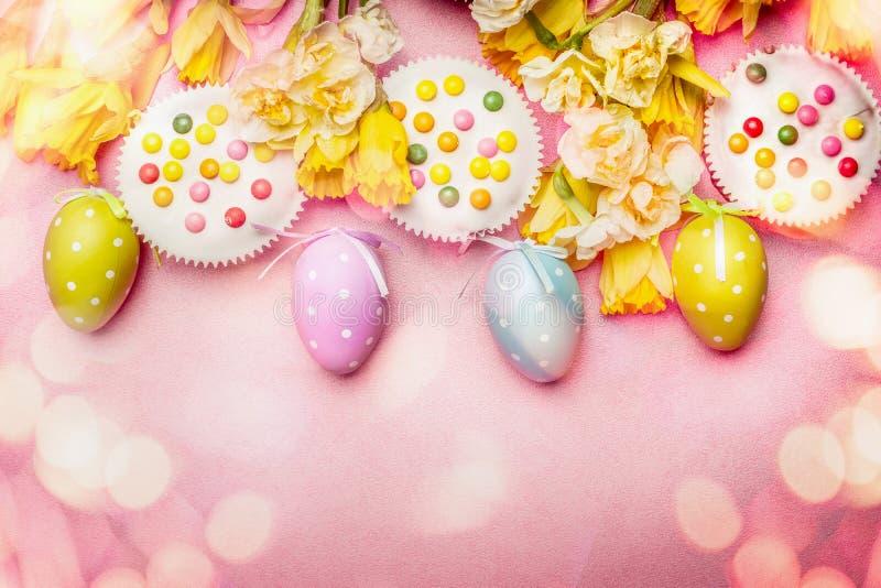 在淡色的可爱的复活节设置与装饰怂恿,花、蛋糕和bokeh照明设备在桃红色苍白背景,顶视图 免版税库存图片