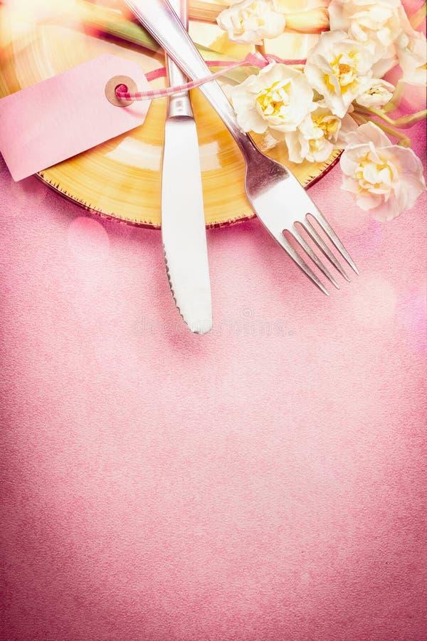 在淡色的可爱的复活节设置与装饰怂恿,花、蛋糕和bokeh照明设备在桃红色苍白背景,顶视图 免版税库存照片