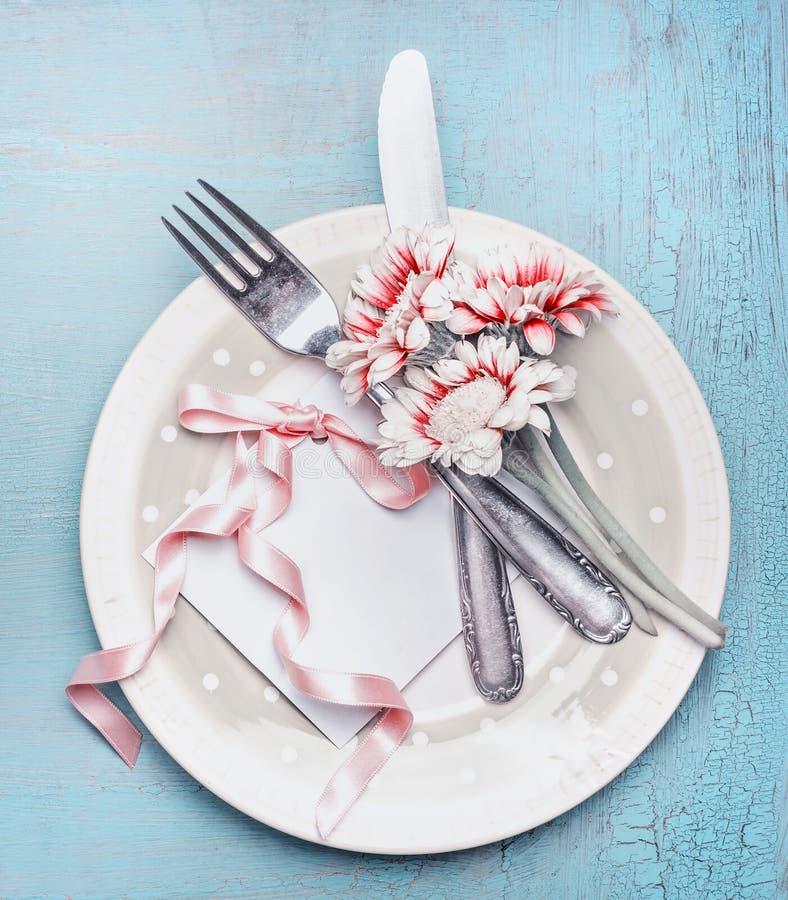 在淡色的可爱的桌餐位餐具与板材、利器、花和卡片与丝带在土耳其玉色破旧的别致 免版税库存图片