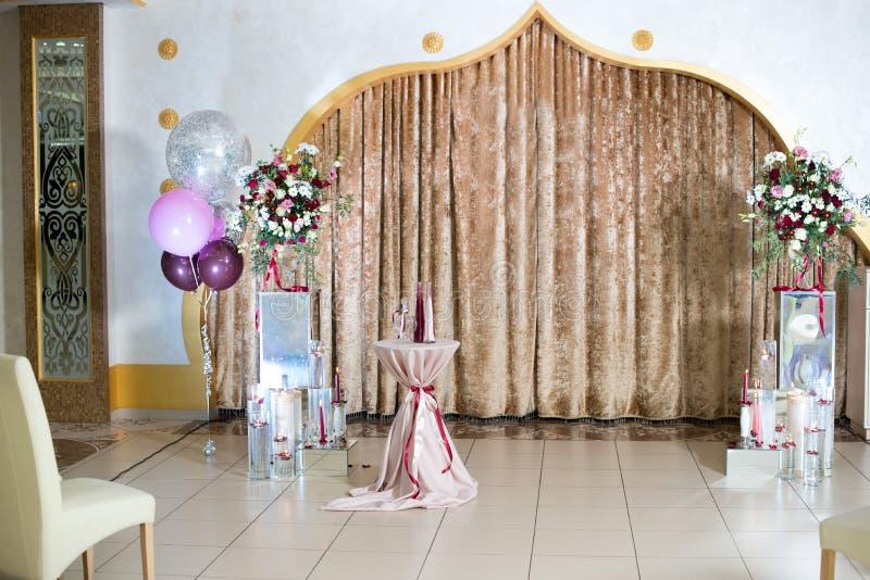 在淡色的婚礼photozone :帷幕,蜡烛,花束,气球 免版税图库摄影