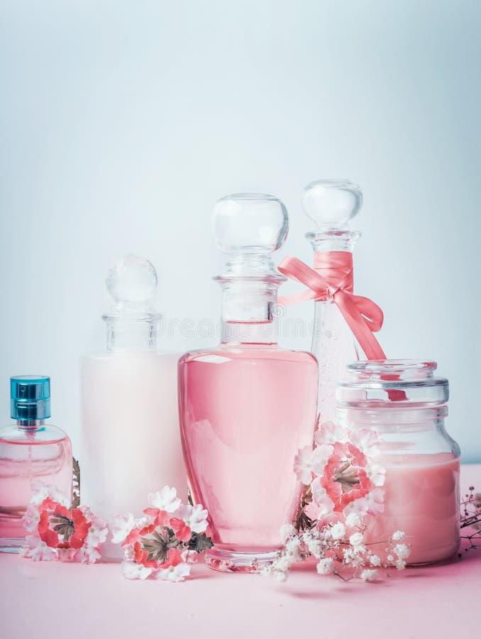在淡色的香水和化妆用品暂短气味 瓶的构成有花的,正面图 库存图片