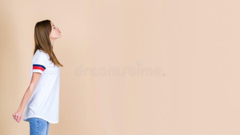 在淡色米黄背景隔绝的迷人的年轻妇女等待的亲吻身分外形  免版税库存图片