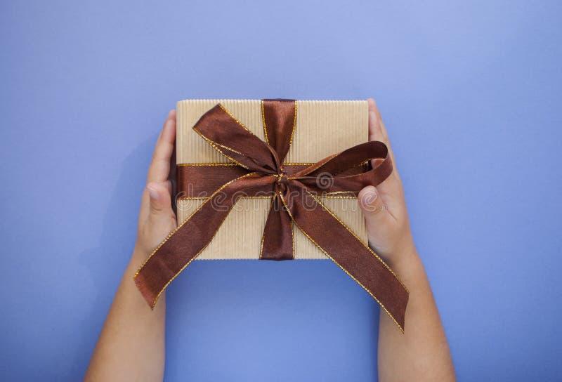 在淡色紫色背景的礼物盒在儿童` s手上 免版税库存照片
