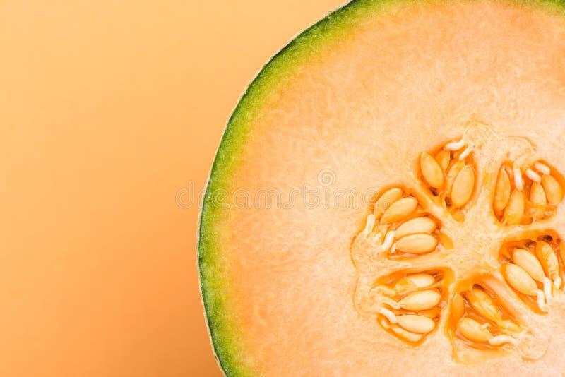在淡色背景的一半切的甜瓜橙色瓜,关闭细节 图库摄影
